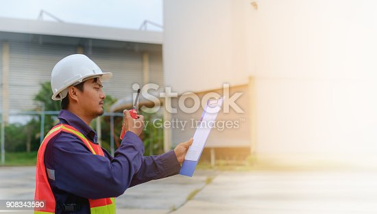 istock Asian engineer in safety uniform and white helmet holding walkie-talkie and clipboard on blurred industry plant background 908343590