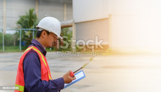 istock Asian engineer in safety uniform and white helmet holding walkie-talkie and clipboard on blurred industry plant background 908343696