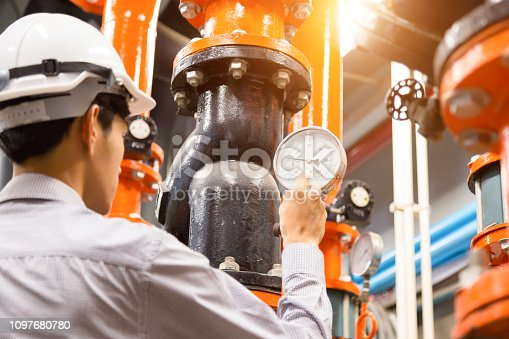 istock Asian engineer maintenance checking technical data of  system equipment Condenser Water pump and pressure gauge , chiller water pump with pressure gauge. 1097680780