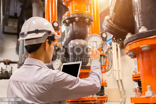 istock Asian engineer maintenance checking technical data of  system equipment Condenser Water pump and pressure gauge , chiller water pump with pressure gauge. 1097681080