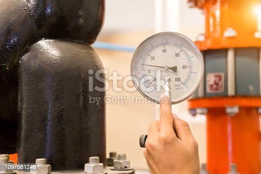 istock Asian engineer maintenance checking technical data of  system equipment Condenser Water pump and pressure gauge , chiller water pump with pressure gauge. 1097681246