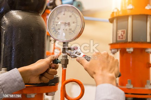istock Asian engineer maintenance checking technical data of  system equipment Condenser Water pump and pressure gauge , chiller water pump with pressure gauge. 1097681294