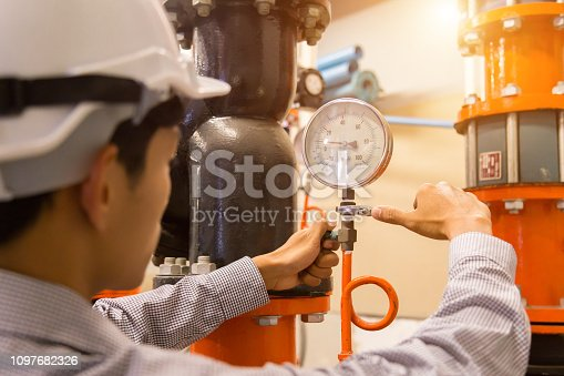 istock Asian engineer maintenance checking technical data of  system equipment Condenser Water pump and pressure gauge , chiller water pump with pressure gauge. 1097682326