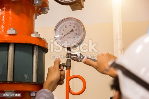 istock Asian engineer maintenance checking technical data of  system equipment Condenser Water pump and pressure gauge , chiller water pump with pressure gauge. 1097682334