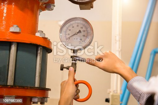 istock Asian engineer maintenance checking technical data of  system equipment Condenser Water pump and pressure gauge , chiller water pump with pressure gauge. 1097682350
