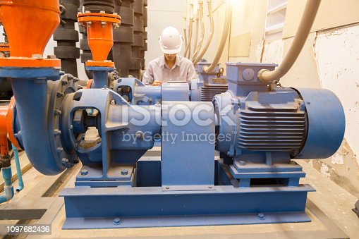 istock Asian engineer maintenance checking technical data of  system equipment Condenser Water pump and pressure gauge ,  water pump. 1097682436
