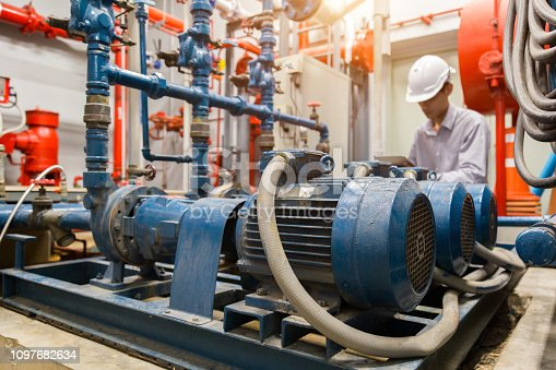 istock Asian engineer maintenance checking technical data of  system equipment Condenser Water pump and pressure gauge ,  water pump. 1097682634