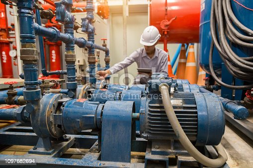 istock Asian engineer maintenance checking technical data of  system equipment Condenser Water pump and pressure gauge ,  water pump. 1097682694