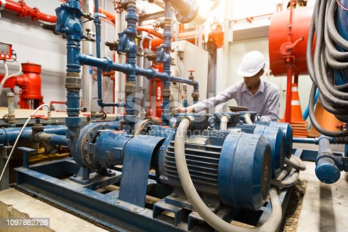 istock Asian engineer maintenance checking technical data of  system equipment Condenser Water pump and pressure gauge ,  water pump. 1097682726
