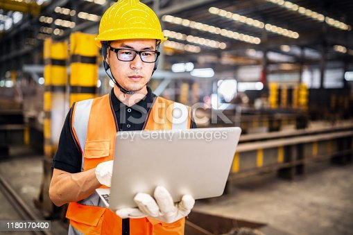 Asian engineer using a laptop in a factory.