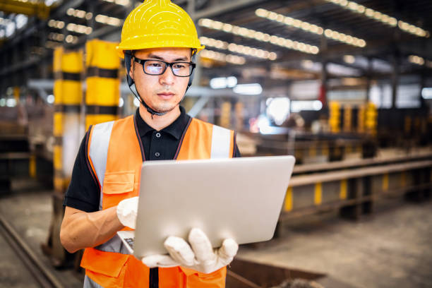 Asian engineer using a laptop in a factory stock photo
