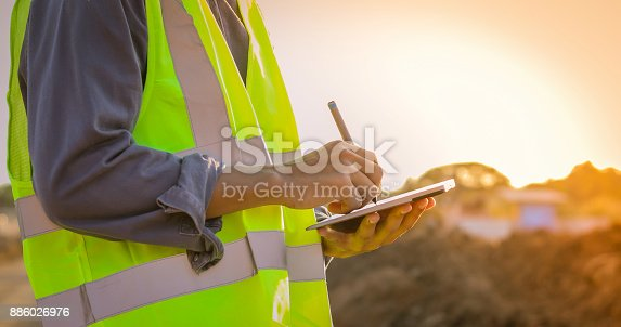 istock Asian engineer with hardhat using  tablet pc computer inspecting and working at construction site 886026976
