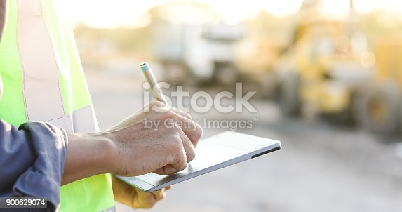 istock Asian engineer with hardhat using  tablet pc computer inspecting and working at construction site 900629074