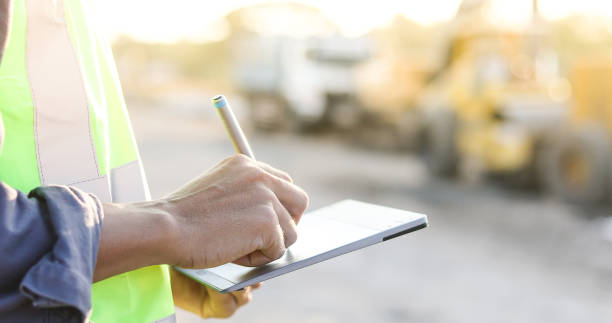 Asian engineer with hardhat using  tablet pc computer inspecting and working at construction site stock photo