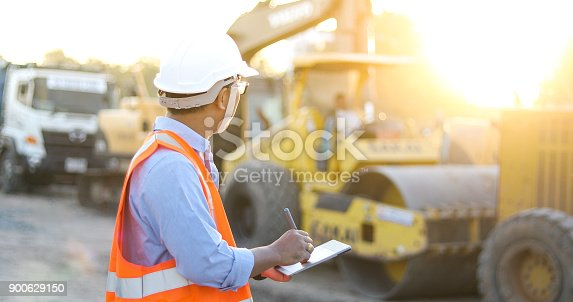 istock Asian engineer with hardhat using  tablet pc computer inspecting and working at construction site 900629150