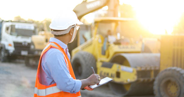 asian engineer with hardhat using  tablet pc computer inspecting and working at construction site - crane construction machinery stock pictures, royalty-free photos & images