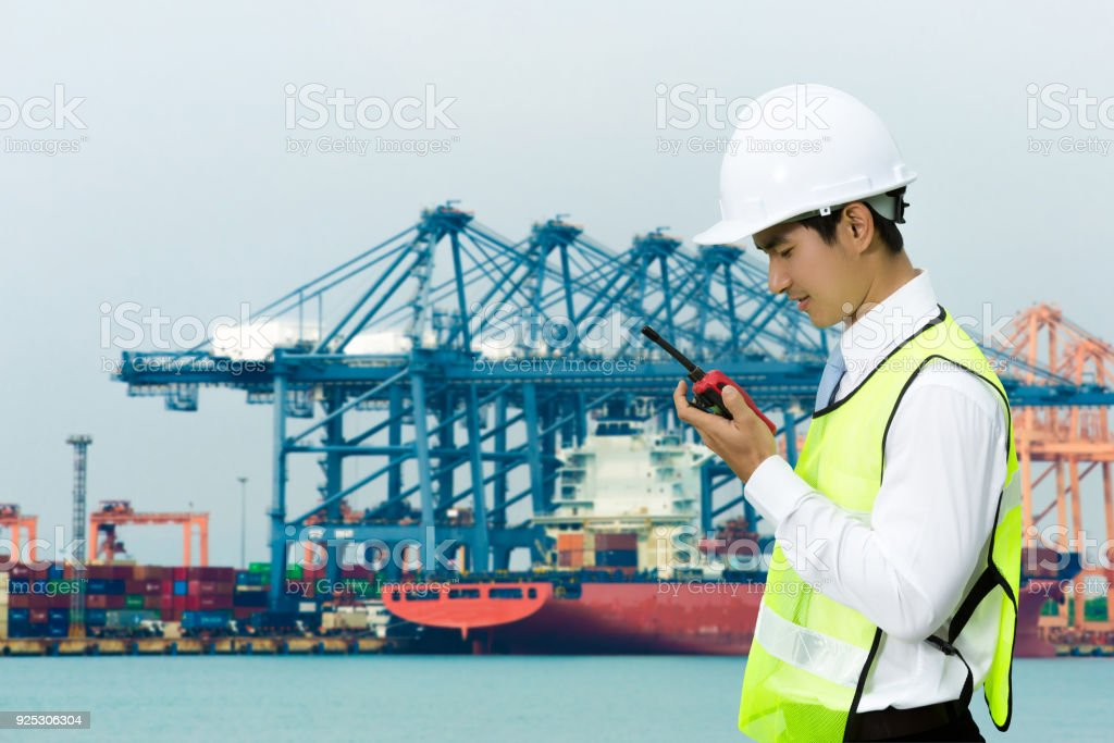 Asian engineers for the men of the shipping port. Using radio with...