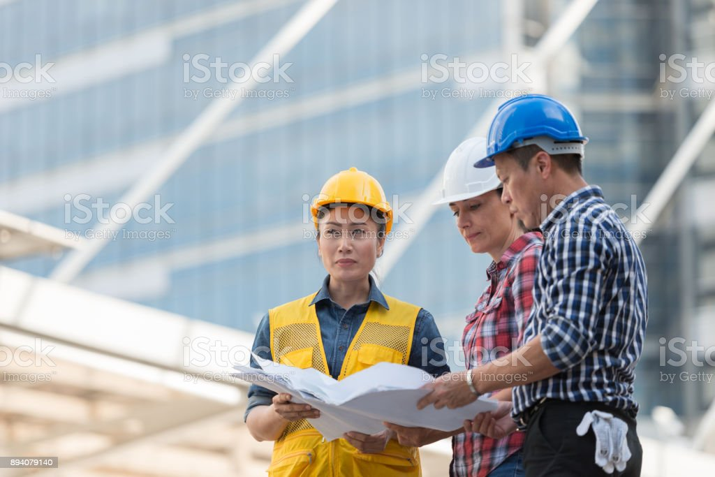 Asian engineers group consult construction on site building asian engineers group consult construction on site building working while holding blueprint paper in city malvernweather Gallery