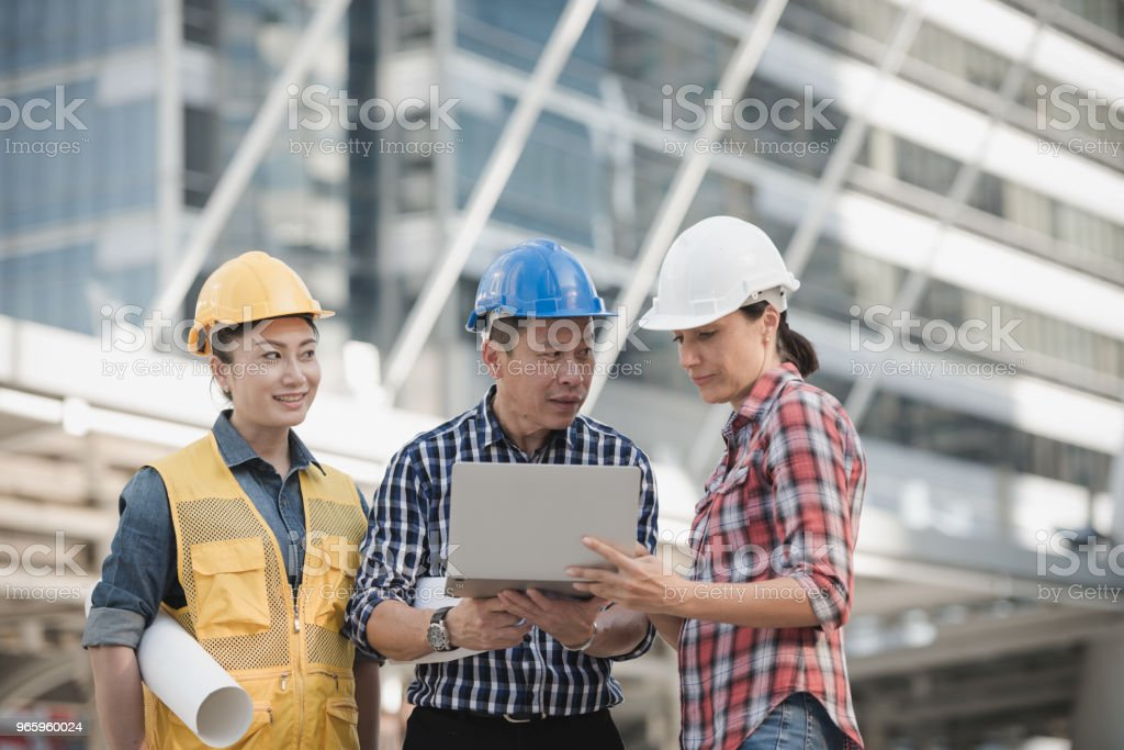 Aziatische ingenieurs groep raadplegen bouw op site gebouw werken terwijl de laptopcomputer en blauwdruk papier. in de achtergrond van de stad. Technologie, teamwerk concept - Royalty-free Architect Stockfoto