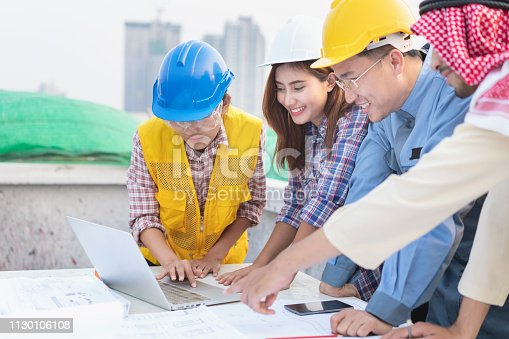 1129095769 istock photo Asian engineers were consulted together and plan in construction site 1130106108