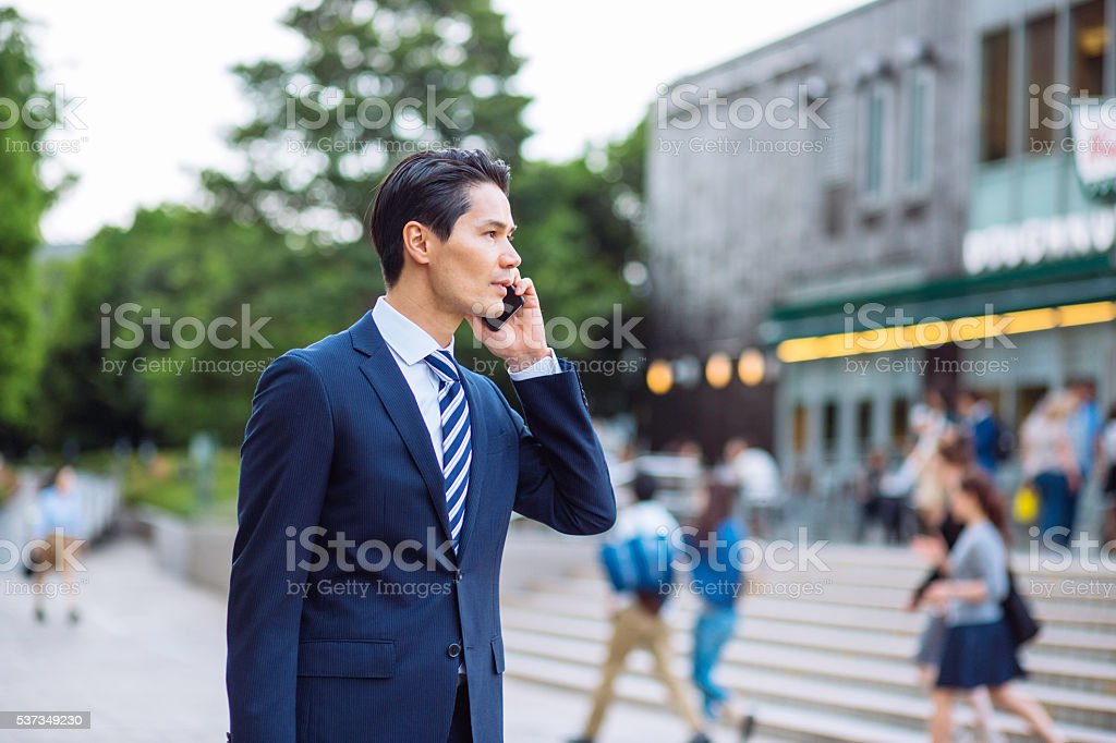 Businessman talking on the phone outdoors at urban setting