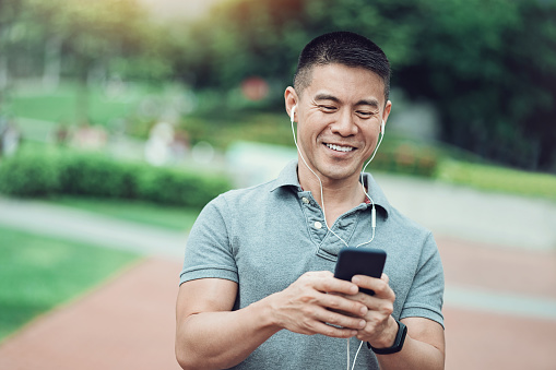 Asian ethnicity man texting in the park