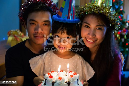 istock Asian family a birthday party for her daughter's daughter is about to blow out the candles. 853303598