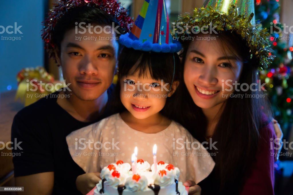Asian family a birthday party for her daughter's daughter is about to blow out the candles. stock photo
