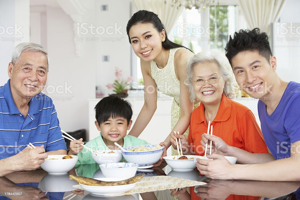 Asian family around the table eating a meal stock photo