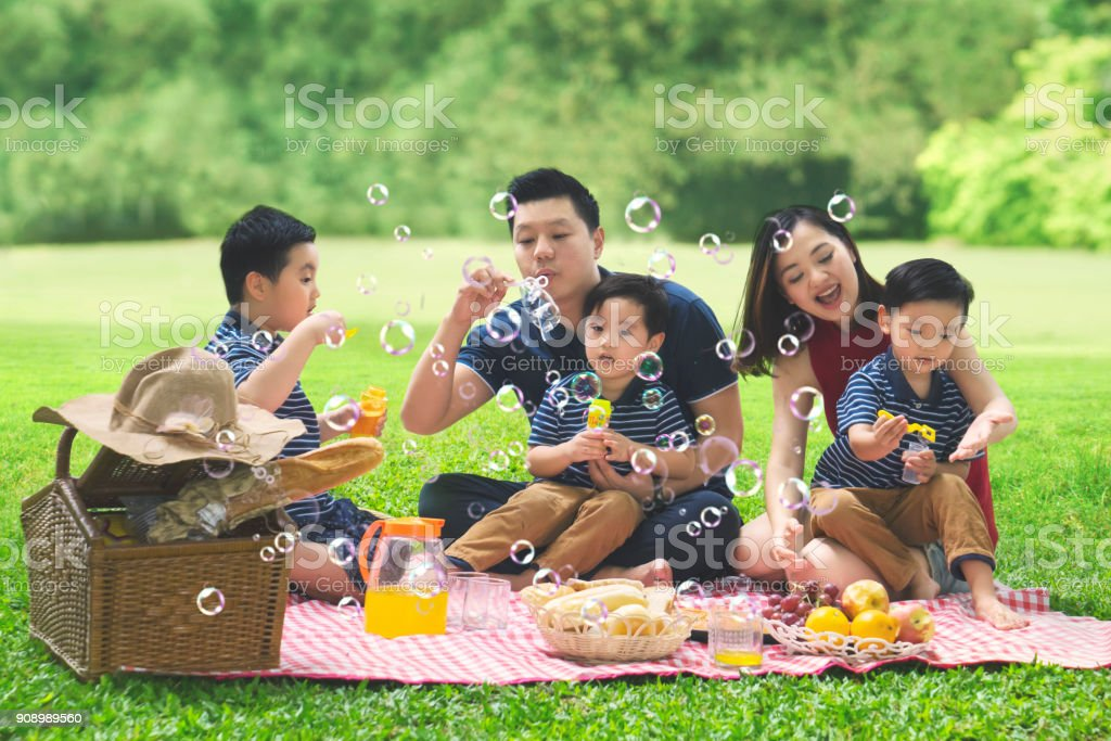 Asian family blows bubble soap in the park stock photo