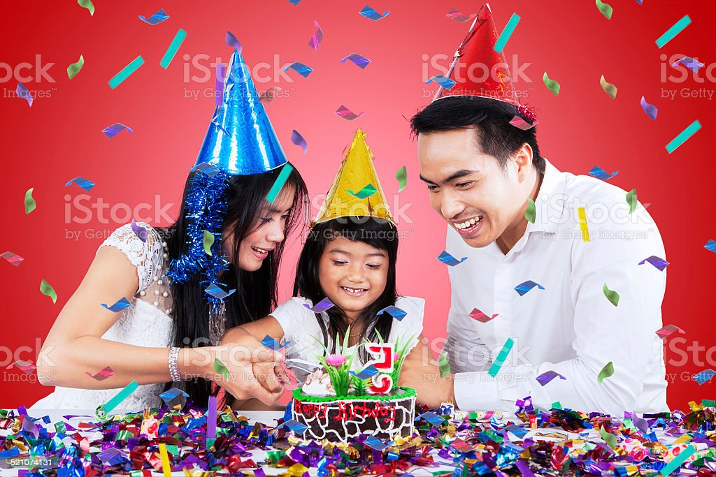 Asian family cutting a birthday cake stock photo