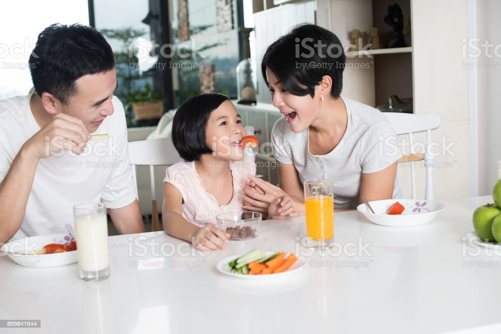 Asian family eating a healthy snack at home. stock photo