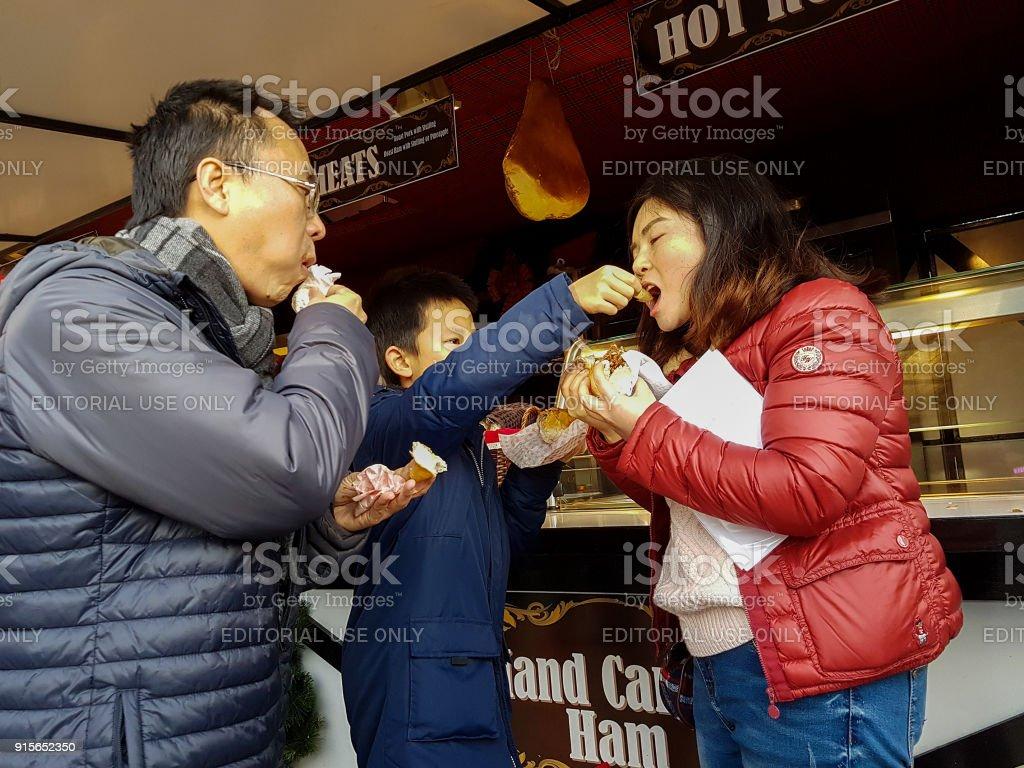 Weihnachtsmarkt Auf Englisch.Asiatische Familie Essen Englisch Hot Dogs Und Warme Sandwiches Aus