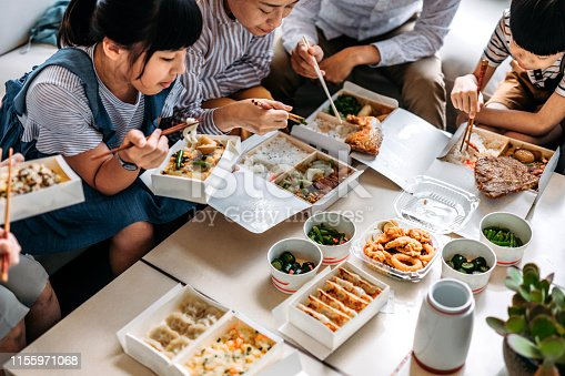 Taiwan family eating takeout food with chopsticks in living room