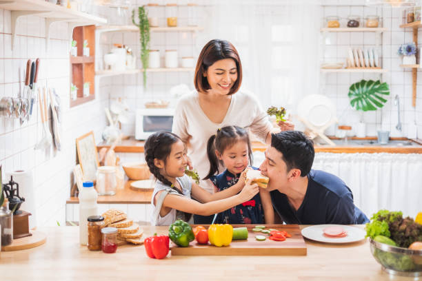 Asian family enjoy playing and cooking food in kitchen at home stock photo