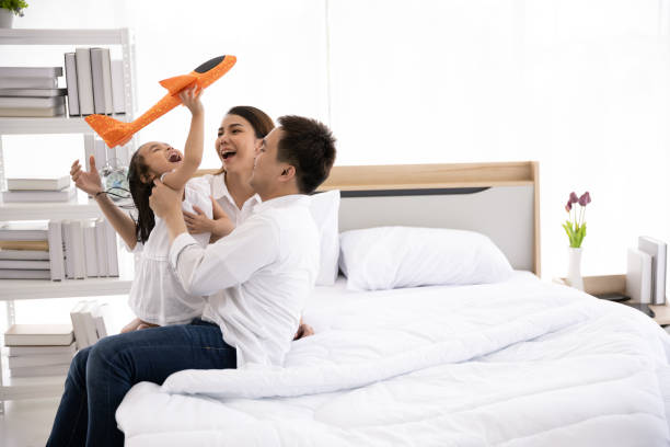 Asian family happy on the bed in the house with sunlight from the window. Father, mother and daughter, aged three are playing with a plane together. Family leisure activities stock photo