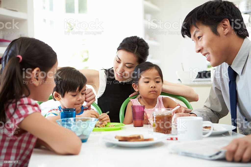 Asian Family Having Breakfast Before Husband Goes To Work stock photo