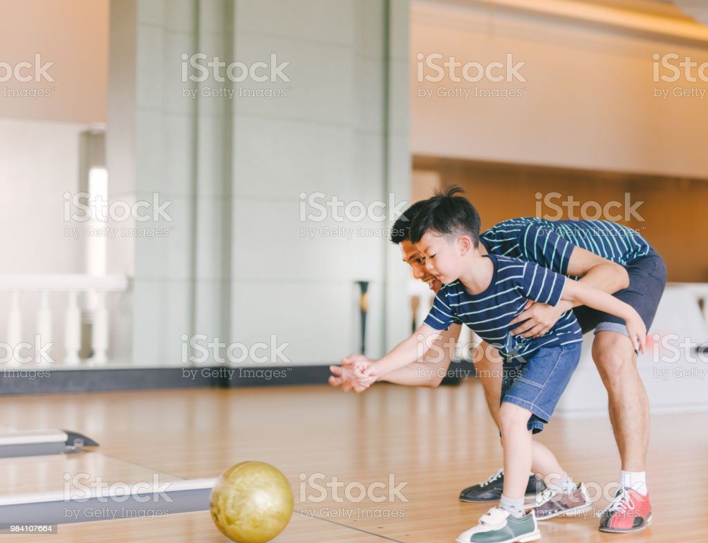 Asian family having fun at bowling club stock photo