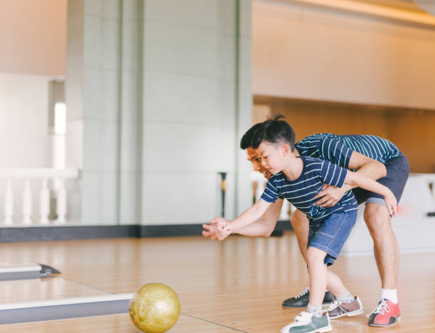 Asian family having fun at bowling club stock photo