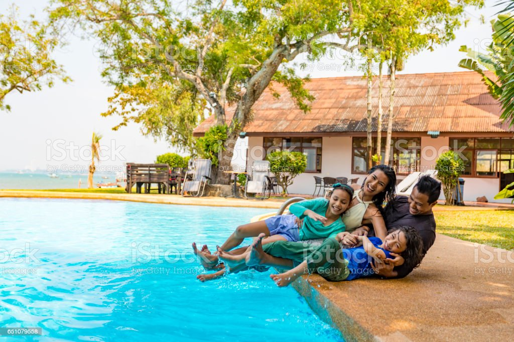 Asian Family Having Fun by the Pool on a Resort Vacation stock photo