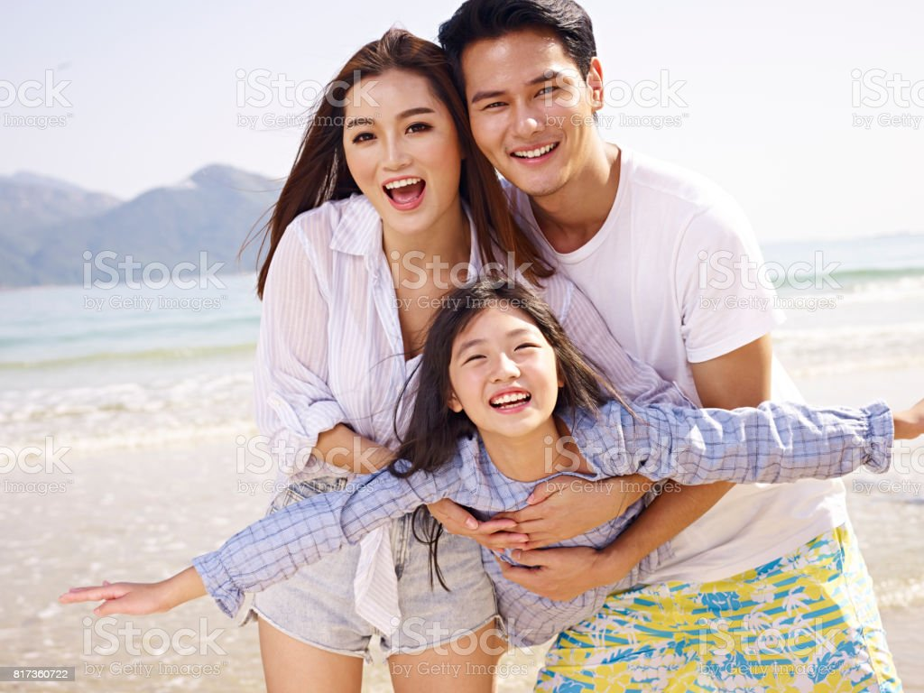 asian family having fun on beach stock photo