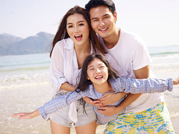 asian family having fun on beach stock photo