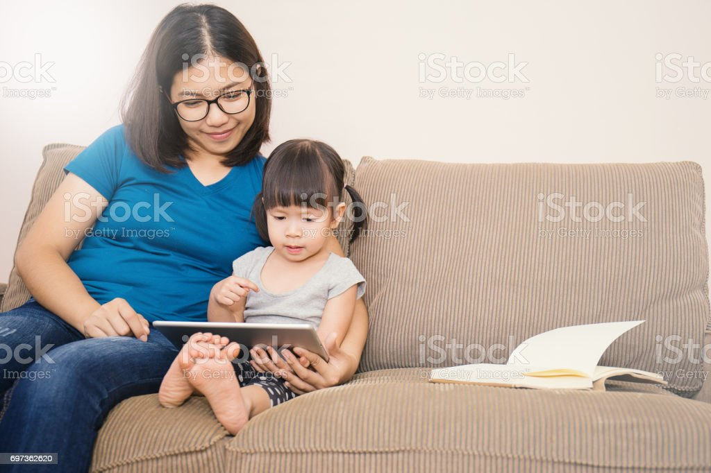 Asian family holding a tablet computer and looking at it stock photo