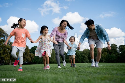589135214 istock photo Asian family holding hands and running at the park 867146706