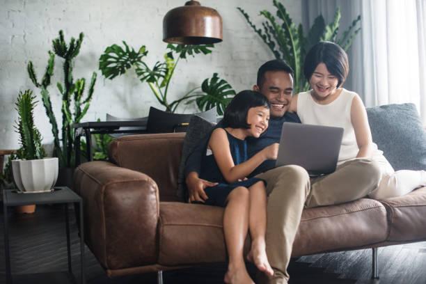 自宅のコンピューターを見てアジアの家族。 - 東洋民族 ストックフォトと画像