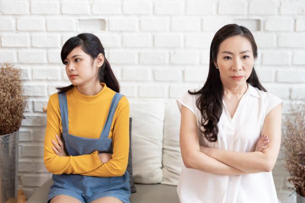 Familia asiática Mamá y adolescente daughte se sienten estresados y enojados, no hablando después de disputa en casa. Concepto de conflicto familiar - foto de stock