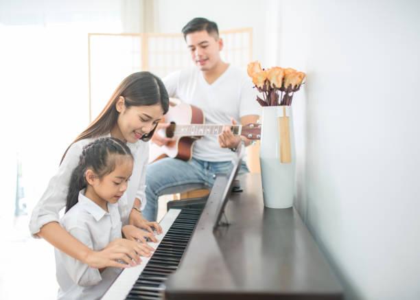 asiatischen familie, mutter und tochter spielt klavier, vater spielte gitarre in familienband zu hause konzept für verwandtschaft - ukulele songs stock-fotos und bilder