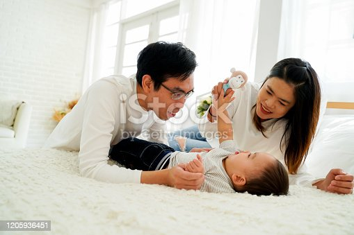 1049923194 istock photo Asian family of father and mother playing toy doll with their son on bed at home 1205936451