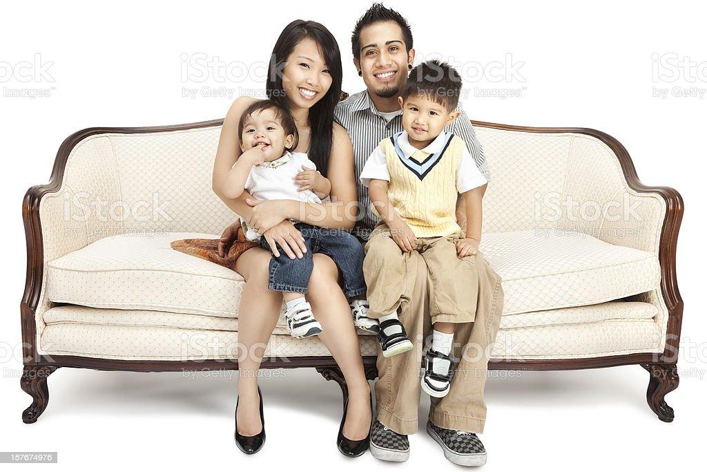 Amazing Asian Family Of Four Sitting On Antique Sofa Royalty Free Stock Photo