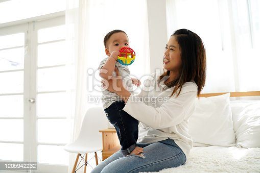 1049923194 istock photo Asian family of mother playing toy doll with their son on bed at home. Young woman carrying baby boy toddler 1205942232
